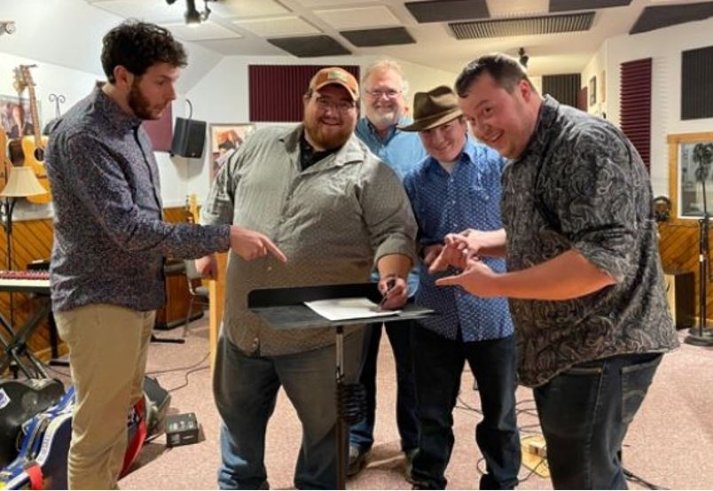 Seth Mulder & Midnight Run putting pen to paper in the presence of Mountain Fever's founder, President and CEO, Mark Hodges.